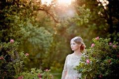 一件鞋带奶油礼服的相当招标金发碧眼的女人以开花的庭院为背景 免版税库存照片
