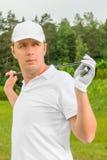 一件T恤杉和一个棒球帽的高尔夫球运动员有高尔夫俱乐部的 图库摄影