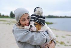 一buldog的小狗在一个温暖的盖帽的在逗人喜爱的妇女的手上 库存图片