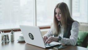 一busines妇女与在咖啡馆的膝上型计算机一起使用 股票视频
