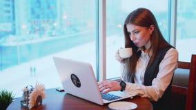 一busines妇女与在咖啡馆的膝上型计算机一起使用 股票录像
