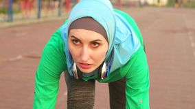 一hijab的女孩回教运动员在低开始 股票录像