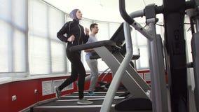 一hijab的女运动员在一台连续模拟器和一个人健身房的,家庭 影视素材