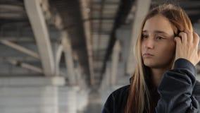 一hoody的一个十几岁的女孩与敞篷和疏松摩擦她的头发的多彩多姿的头发,离开敞篷和看 股票录像