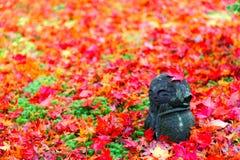 一Warabe Jizou石雕刻的特写镜头视图与一个可爱的孩子的图象在用下落的叶子报道的地面上的 免版税库存照片