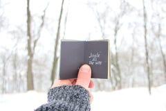 丁当一直 圣诞节歌曲激动人心的行情,拿着与题字的人一本书 免版税库存照片