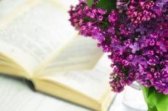 丁香和书 春天花花束以一开放书说谎为背景的 免版税图库摄影