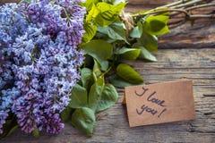 丁香开花与文本的花束和工艺纸我爱你在Th 免版税图库摄影