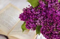 丁香春天花花束以一本开放书为背景的 免版税库存图片