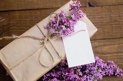丁香花束在一张木桌上的与礼物盒 免版税库存图片