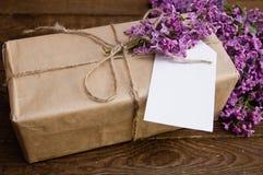 丁香花束在一张木桌上的与礼物盒 免版税库存照片
