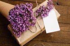 丁香花束在一张木桌上的与礼物盒 库存照片