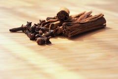 丁香香料在一个木板的肉桂条 免版税库存图片