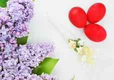 丁香,复活节蜡烛和红色鸡蛋 库存图片