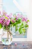 丁香仍然开花在玻璃花瓶的束在窗口 免版税库存图片