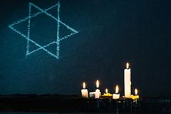 七个灼烧的蜡烛和大卫王之星反对 库存图片