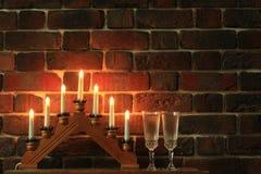 七个蜡烛和酒杯用香槟在砖墙附近 免版税图库摄影