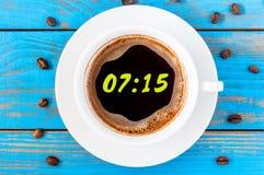 七十五小时或7:15在早晨咖啡喜欢一个圆的时钟表盘 在蓝色木背景的顶视图 免版税库存照片
