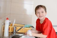 七岁的男孩在厨房里洗盘子 免版税库存照片