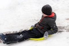 七岁的男孩在绿色冰雪撬乘坐幻灯片,在小山下 冬天活动、休闲和孩子的概念 免版税库存照片