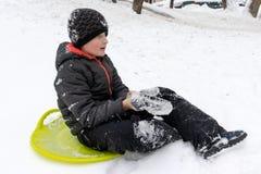 七岁的男孩坐准备好一个绿色塑料茶碟的雪撬乘坐幻灯片 冬天活动的概念,休闲 图库摄影