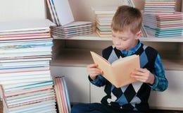 七岁的男孩殷勤地读坐在书中的书 图库摄影
