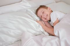 七岁的男孩醒了和笑,当在床上时 免版税库存图片