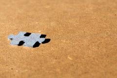 七巧板在对木棕色背景的透视看的纸板片断 免版税库存照片