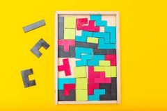 七巧板比赛木和五颜六色在黄色背景 平的位置 库存照片