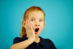 七年的红发女孩特写镜头画象激动显著的,投入他的手对面颊,表示惊奇 免版税库存图片