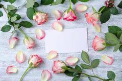 七有一张白色卡片的玫瑰色的开花和瓣在葡萄酒木背景 图库摄影