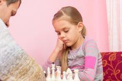 七年女儿考虑接下来的步骤,下棋 免版税库存图片