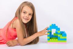 七年女孩在框架修建了设计师神色和乐趣房子  图库摄影