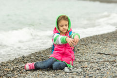 七年女孩坐温暖的衣物的Pebble海滩和通过她的手指小石头倾吐  免版税库存照片