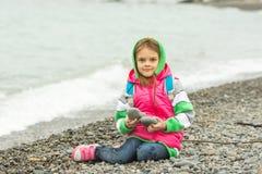 七年女孩坐温暖的衣裳的在框架的Pebble海滩和神色 库存图片