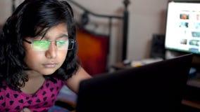 万人迷在家工作在膝上型计算机戴着眼镜眼镜办公室的女孩印度亚裔白种人 关闭在眼睛玻璃反射 股票录像