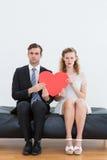 万人迷夫妇坐长沙发 库存照片