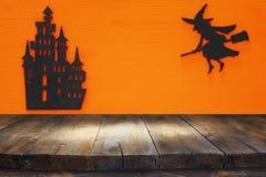 万圣夜与空的土气桌的假日概念在橙色背景 为产品显示蒙太奇准备 免版税库存图片