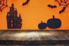 万圣夜与空的土气桌的假日概念在橙色背景 为产品显示蒙太奇准备 库存照片