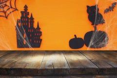 万圣夜与空的土气桌的假日概念在橙色背景 为产品显示蒙太奇准备 库存图片