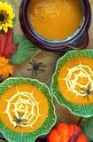 万圣夜与蜘蛛网酸性稀奶油装饰的南瓜汤 免版税库存图片