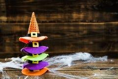 万圣夜与逗人喜爱的小的巫婆帽子的卡片概念在蜘蛛网 免版税库存照片