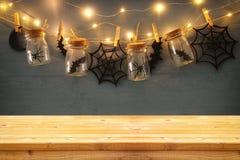 万圣夜假日概念 在masson前面的空的老木桌刺激与蜘蛛和浴装饰 库存图片
