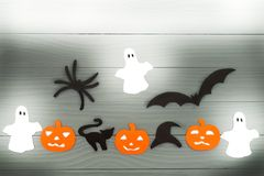 万圣夜假日背景用三个南瓜、猫、蜘蛛、棒、帽子和三个鬼魂 免版税库存照片