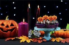 万圣夜党桌用巧克力杯形蛋糕,蜘蛛,南瓜 免版税图库摄影