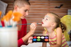 万圣夜党的年轻母亲绘画女儿面孔 万圣夜或狂欢节家庭生活方式背景 库存图片