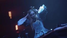 万圣夜公主服装的DJ女孩和圣诞老人muerte面孔油漆在场面跳舞 股票录像
