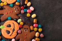 万圣夜南瓜、棒和姜饼人吸血鬼曲奇饼和五颜六色的糖果顶上的射击与拷贝空间 图库摄影