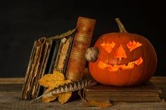 万圣夜南瓜和咒语书  被雕刻的南瓜 登记魔术 传统的节假日 免版税库存图片