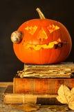 万圣夜南瓜和咒语书  被雕刻的南瓜 登记魔术 传统的节假日 免版税图库摄影